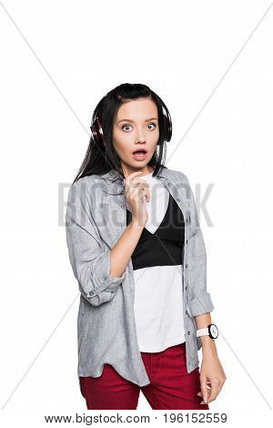 Shocked Beautiful Girl Listening Music In Headphones And Looking At Camera Isolated On White