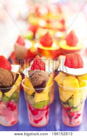 Fruits pieces in a plastic cup take away ready to eat on a market stall close up. Fruit salad to go