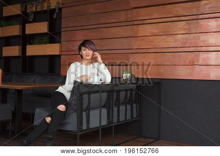 Young pretty woman sitting in cafe and looking at camera having cup of coffee.