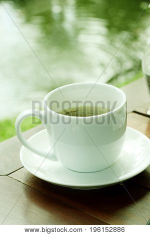 Cup of coffee on wooden table in garden.