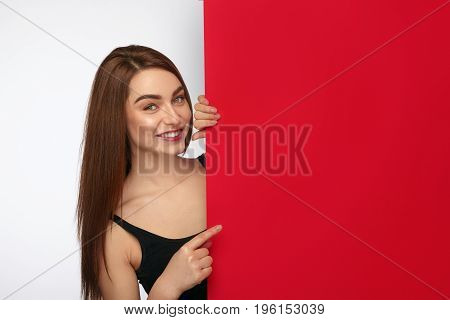 Smiling young girl hiding behind big red sheet of paper and pointing on a side.
