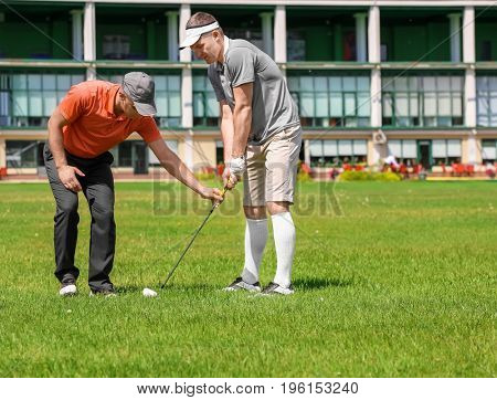 Caddy teaching young man to play golf on course in sunny day