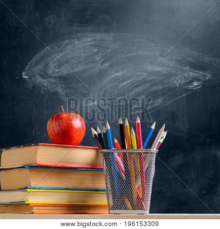 Back to School. Accessories, books and fresh apple against chalkboard