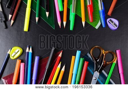 School accessories, books and fresh apple against black background