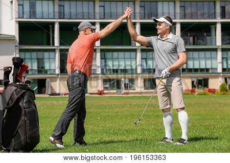 Young men on golf course in sunny day