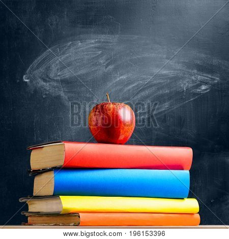 Back to School. Books and fresh apple against chalkboard