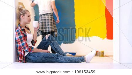 Happy couple doing home renovations, the man is painting the room and the woman is relaxing on the floor and drinking coffee