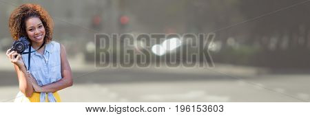 Digital composite of Millennial woman with camera against blurry street