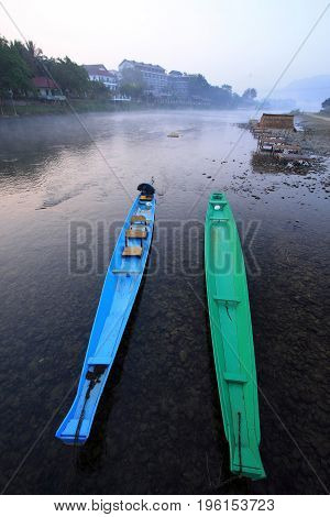 a blue boat and a green boat float side by side in a small river.