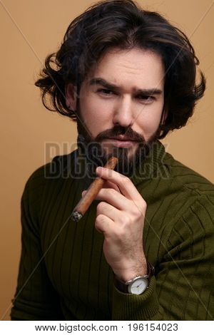 Young bearded man in sweater looking at camera while holding cigar.