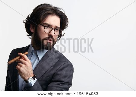 Stylish confident businessman smoking a cigar and looking away isolated on white.