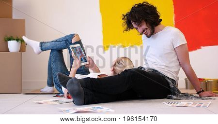 Happy young couple relaxing after painting a room in their new house on the floor