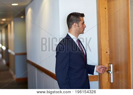 business, security and people concept - businessman with keycard at hotel room or office door