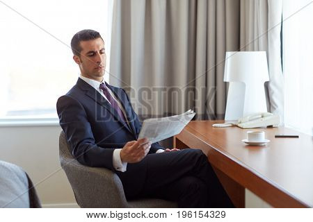 business, people and mass media concept - businessman reading newspaper and drinking coffee at hotel room