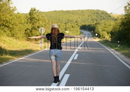 Woman On the middle of the road in mountains. Forty Years old woman on the road