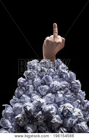 Cropped Shot Of Hand Showing Middle Finger While Reaching Out From Heap Of Crumpled Papers Isolated