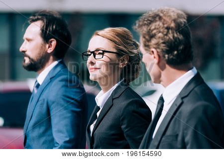Beautiful Blonde Businesswoman Standing Between Confident Middle Aged Businessmen