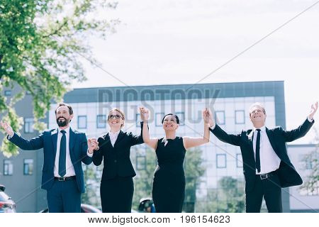 Triumphing Multiethnic Businesspeople Holding Hands While Standing Together Outside