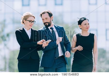 professional team of middle aged multiethnic businesspeople walking together and talking in city