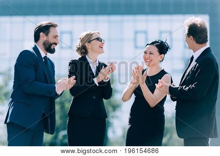 Cheerful Multiethnic Businesspeople Applauding While Standing Together On Street
