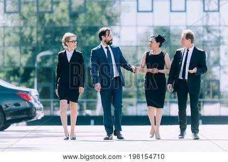 Multiethnic Group Of Professional Middle Aged Businesspeople Walking Together And Talking On Street