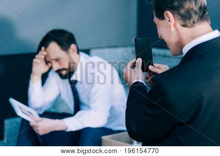Smirking Businessman Holding Smartphone Holding Smartphone And Photographing Upset Fired Colleague S