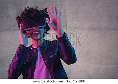 Young cheerful female in leather jacket wearing VR glasses and holding hand up on wall background.