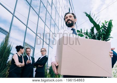 Fired Middle Aged Businessman Holding Cardboard Box While Colleagues Standing And Talking Behind