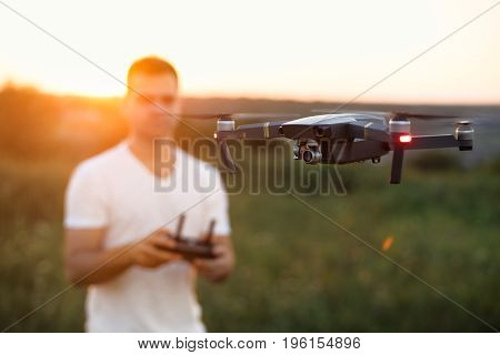 Drone hovers in front of man with remote controller in his hands. Quadcopter flies near pilot. Guy taking aerial photos and videos