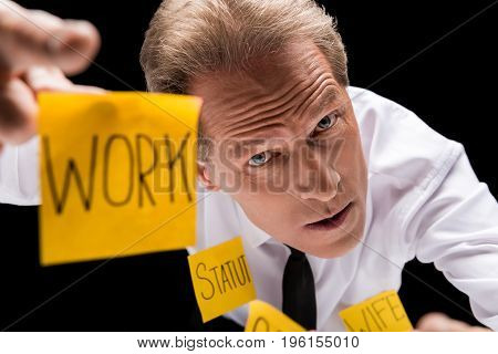 Stressed Middle Aged Businessman With Sticky Notes On Clothes Pointing At Camera Isolated On Black