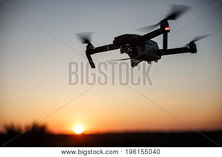 Small compact quadcopter flies in the air on sunset outdoors. Drone hovers and stays stable.