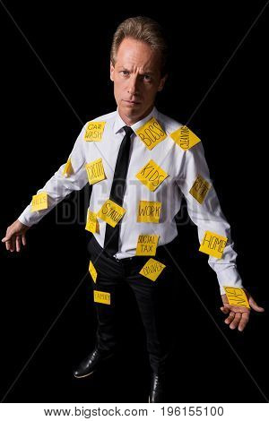 Frustrated Middle Aged Businessman With Sticky Notes On Clothes Looking At Camera Isolated On Black