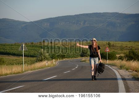 Woman hand hitchhiking and asking for a ride. Forty Years old woman on the road
