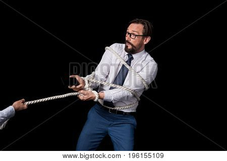 Cropped Shot Of Hand Pulling Rope With Tied Businessman Holding Smartphone Isolated On Black