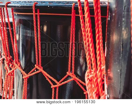 Knots from red ropes of taiko drums o-kedo close up background. Musical instrument of Asia.