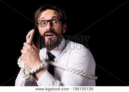 Scared Middle Aged Businessman Tied With Rope Talking On Smartphone Isolated On Black