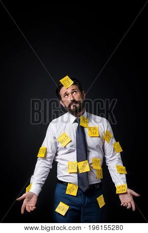 Frustrated Middle Aged Businessman With Sticky Notes On Clothes Looking Up Isolated On Black
