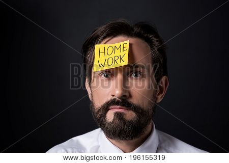 Upset Middle Aged Businessman With Home Work Lettering On Sticky Note On Forehead Looking At Camera