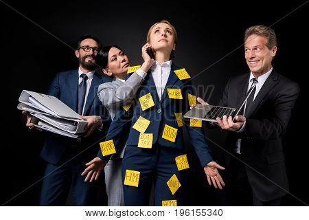 Stressed Mature Businesswoman With Sticky Notes On Clothes Standing Between Colleagues Holding Folde