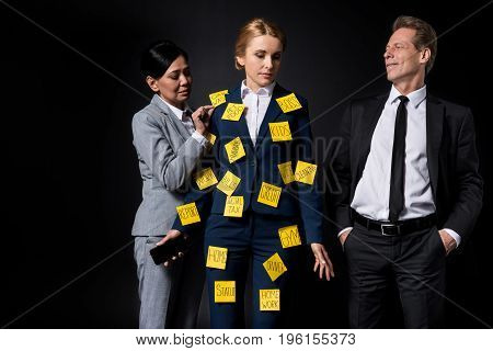overworked middle aged businesswoman with sticky notes on clothes holding smartphone while standing with colleagues isolated on black