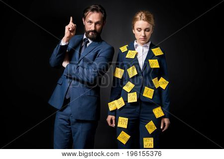 Stressed Businesswoman With Sticky Notes On Clothes Standing Near Bearded Businessman Pointing Up Wi
