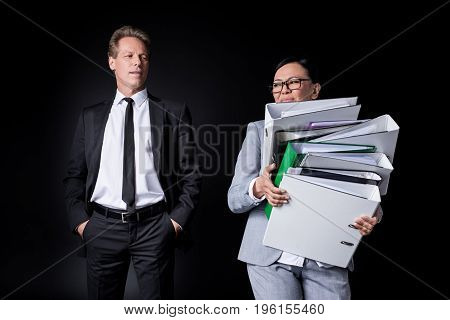 Confident Mature Businessman With Hands In Pockets Looking At Female Colleague Holding Pile Of Folde