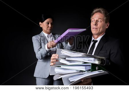 Frustrated Mature Businessman Holding Pile Of Folders While Female Colleague Putting Folder On The T