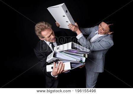 Excited Asian Businesswoman With Folder Fighting With Scared Businessman Holding Folders Isolated On