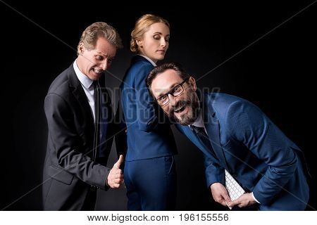 Businessman Touching Buttocks Of Female Colleague While Male Colleague Laughing At Camera, Sexual Ha