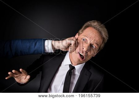 Cropped Shot Of Hand Punching Middle Aged Businessman Isolated On Black