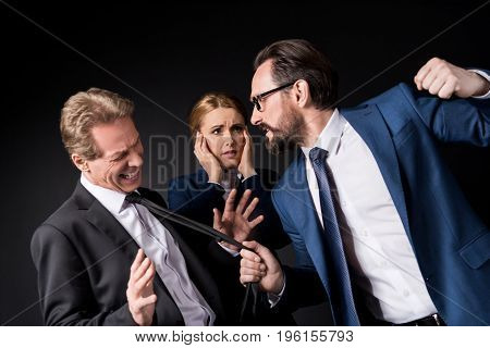 Mature Businessmen Fighting While Scared Businesswoman Standing Behind Isolated On Black