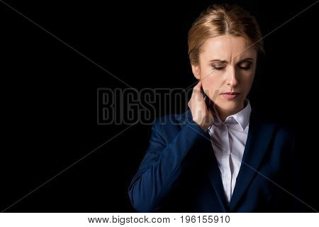 Tired Middle Aged Business Woman With Headache Holding Hand On Neck Isolated On Black
