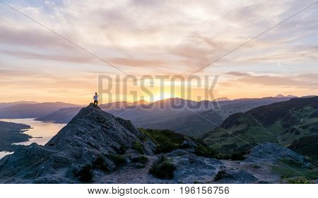 Lady enjoys the view from the mountain top as the sunset below the horizon