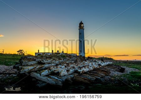 Tall light house towers over remains of a old ship wreck at sunset
